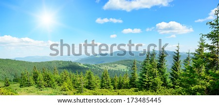High mountains and sun on blue sky                                     - stock photo