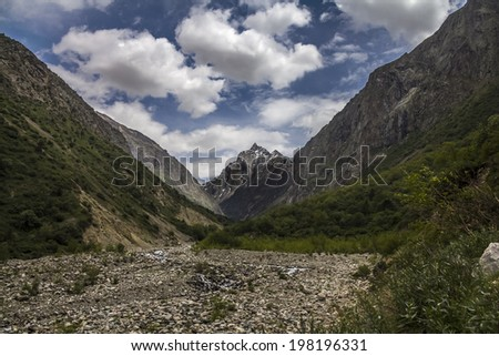 High mountains valley under cloudy sky - stock photo