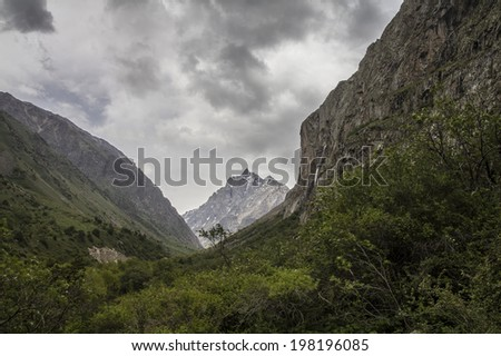 High mountains valley under heavy clouds - stock photo