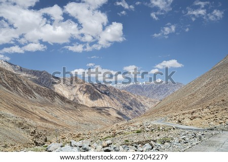 High mountains winding asphalt road among snowy peaks view - stock photo