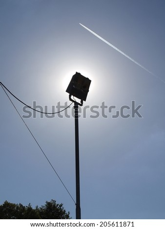 High outdoor lam post with plugged wires, the plane is flying on sky in background.