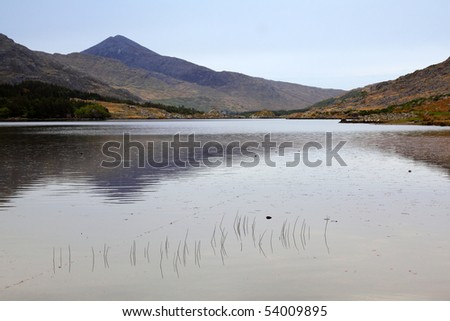 high peak of Corrantouhill Mountain reflected in Cummenduff Lake in The Black Valley, Co.Kerry, Ireland - stock photo