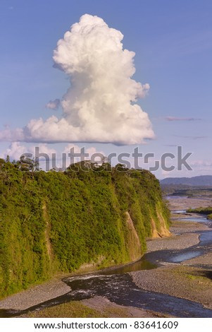 High point of view of Ecuadorian river with a big cumulus cloud - stock photo