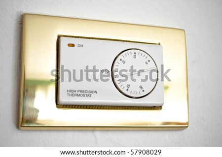 High precision thermostat on a white wall - stock photo