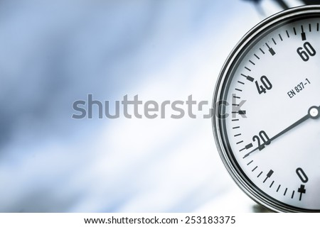 High pressure reading on gas wellhead against the background of dark sky  - stock photo