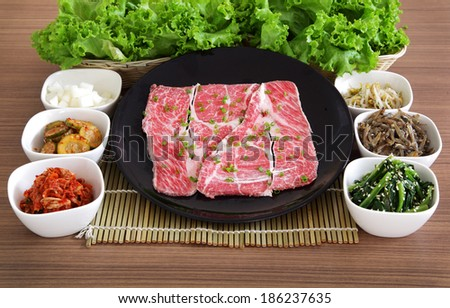 high quality premium Fresh Beef slices on white plate korean grilled menu with vegetable and sauces  - stock photo
