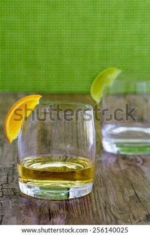 High quality tequila in a snifter with orange garnish and silver tequila in blurred background - stock photo