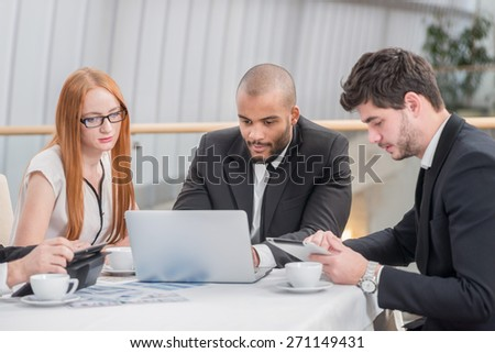High quality work in the office. Four confident successful businessmen at a meeting while sitting at a table discussing business affairs in the office - stock photo