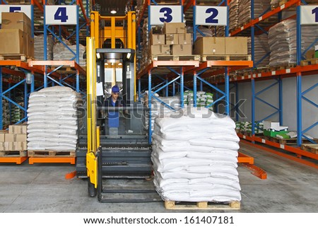 High rack forklift stacker in distribution warehouse - stock photo