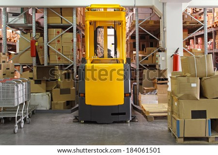 High rack stacker forklift truck in distribution warehouse - stock photo