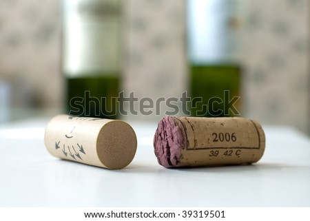 High resolution image of corks and bottles of wine. This image has shallow dept of field with corks in foreground and bottles of wine in the background. - stock photo