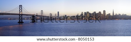 High-resolution panoramic image of Bay Bridge and San Francisco downtown decorated by Christmas lighting at dusk (shot from Treasure Island). Copyspace on - stock photo