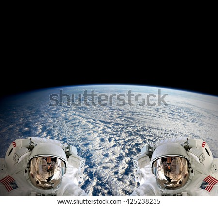 High resolution planet Earth two astronauts spaceman helmet suit floating people outer space walk. Elements of this image furnished by NASA. - stock photo