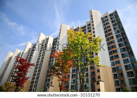 high rise apartment building with trees in front - stock photo