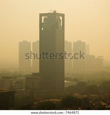 High rise building at sunrise – in a polluted city - stock photo