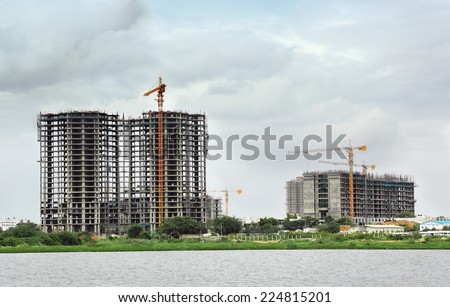 High-rise building construction using tower cranes and other construction equipment - stock photo