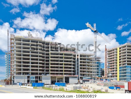 High-rise building under construction. The site with cranes against blue sky - stock photo