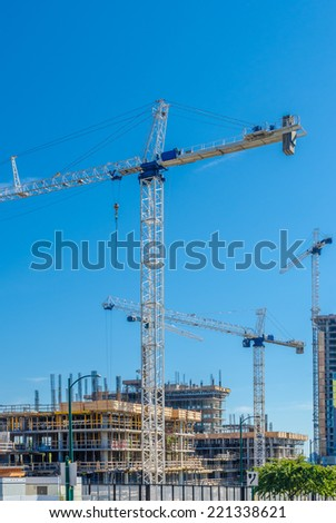 High-rise building under construction. The site with cranes against blue sky. Vancouver, Canada. Vertical.