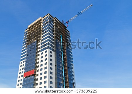 High-rise building under construction with a crane working on the background of the sky - stock photo