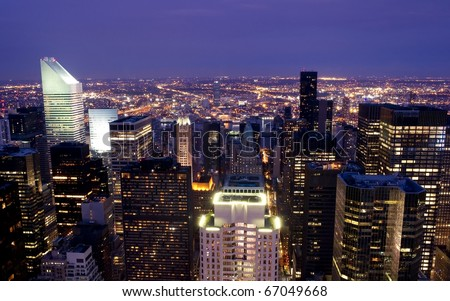 High rise buildings lighting up during sunset in New York City - stock photo
