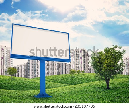 high-rise buildings of same design over green hills with a few trees, blank billboard and tree on foreground - stock photo