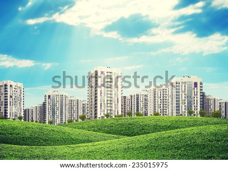 high-rise buildings of same design over green hills with low trees - stock photo