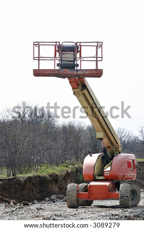 High rise cherry picker on construction site - stock photo