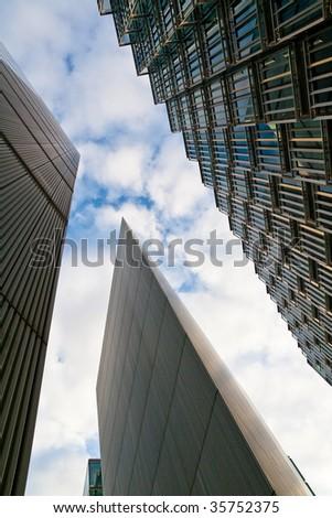 high rise city skyscraper under blue sky in london, the world financial hub - stock photo