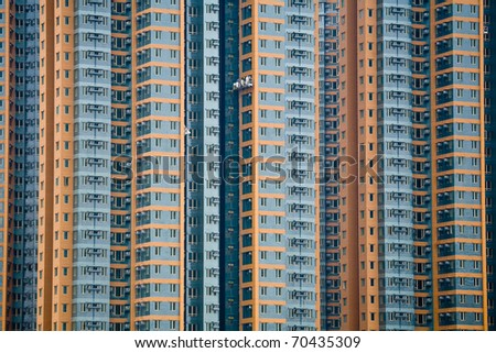 High rise flats in blue and orange with window cleaners - stock photo