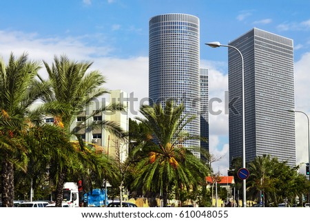 High rise modern buildings with palm trees in downtown area of Israel on sunny day against blue skies.