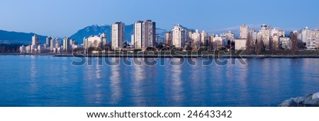 High-rises at English Bay, Vancouver, Canada are lit by the last rays of setting sun. - stock photo