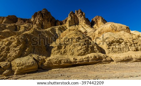 High sandstone cliffs painted in many glowing shades of orange, gold and red. Narrow canyon with vertical walls on both sides. Rocky landscape background. Golden canyon, Death Valley - stock photo