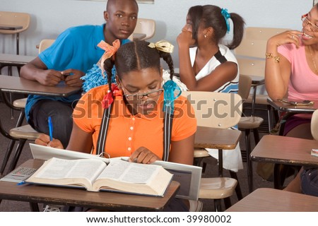 High school classroom with four children, one boy and three girls socializing - stock photo