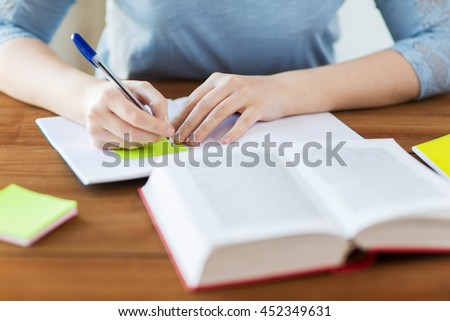 high school, education, people and learning concept - close up of young student or woman with book and notebook writing on sticker at home - stock photo