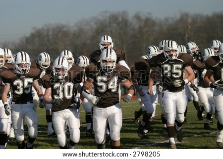 High school football players charging on to the field. Editorial use.