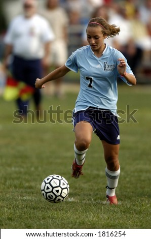 high school girl soccer player about to make a move with the soccer ball - stock photo