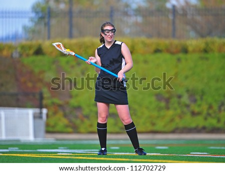 High school girls lacrosse player in her black uniform and socks cradling the ball. - stock photo