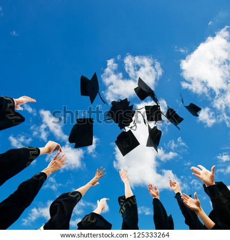 high school graduates tossing up hats over blue sky.