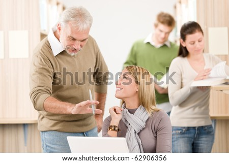 High school library - female student with mature professor - stock photo