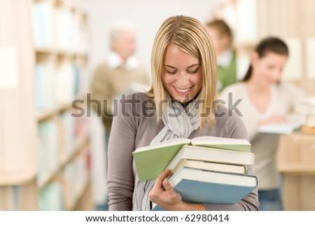 High school library - happy female student with book read - stock photo