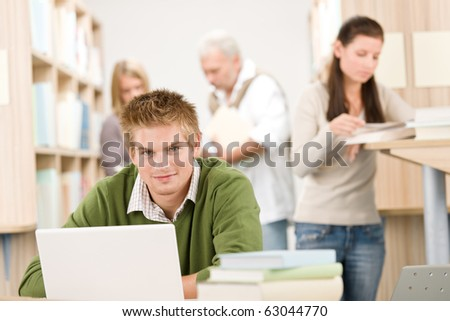 High school library - Student with book and laptop - stock photo