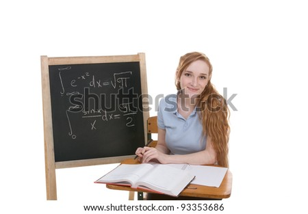 High school or college Caucasian redhead woman student sitting by the desk. Blank blackboard with advanced mathematical formulas is visible in background - stock photo
