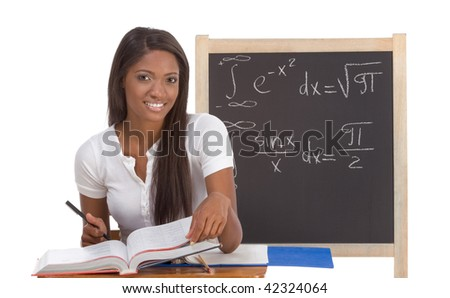 High school or college ethnic African-American female student sitting by the desk at math class. Blackboard with advanced mathematical formals is visible in background - stock photo