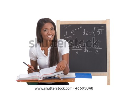 High school or college ethnic African-American female student sitting by the desk at math class. Blackboard with complicated advanced mathematical formals is visible in background