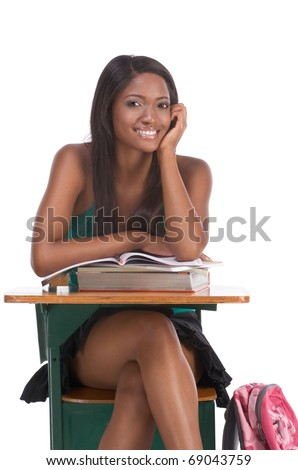 High school or college ethnic African-American female student sitting by the desk with books and copybook in class - stock photo