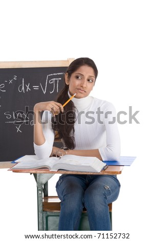 High school or college ethnic Indian female student sitting by the desk at math class. Blackboard with advanced mathematical formals is visible in background