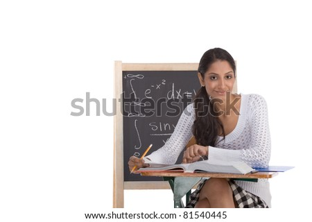 High school or college ethnic Indian female student sitting by the desk at math class. Blackboard with advanced mathematical formals is visible in background - stock photo