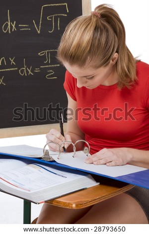 High school or college female student sitting by the desk at math class. Blackboard with advanced mathematical formals is visible in background - stock photo