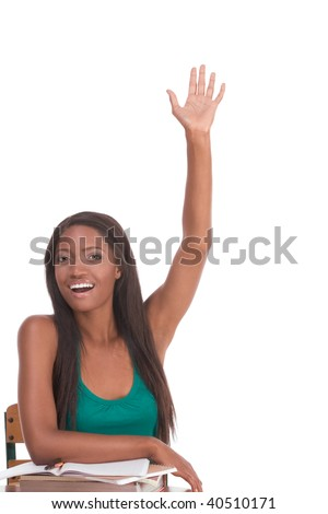 High school or college female student sitting by the desk raising her arm signaling that she know and is ready to answer and eager to participate - stock photo