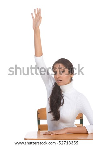 High school or college female student sitting by the desk raising her arm signaling that she know and is ready to answer